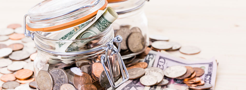 Photo of a jar overflowing with coins and bills. (c) Can Stock Photo